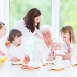 Grandmother enjoying breakfast with her daughter and grandchildren — Stock Photo