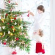 Toddler girl helping her brother to decorate a beautiful Christmas tree — Stock Photo