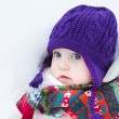 Baby girl wearing a warm winter hat and a colorful scarf — Stock Photo