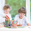 Toddler girl sitting on a white desk watching her brother drawing — Stock Photo #43248935