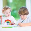 Toddler girl sitting on a white desk watching her brother drawing — Stock Photo #43248975