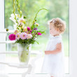 Toddler girl watching flowers in a big vase — Stock Photo #43249061