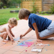 Brother and his baby sister painting with colorful chalk — Stock Photo