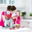 Irl and her young mother making fresh strawberry juice — Stock Photo #43249203