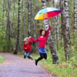 Mother and son under a colorful umbrella — Stock Photo #43249255