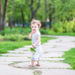 Baby girl walking in a beautiful summer garden — Stock Photo #43249395