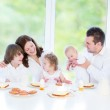 Young family with three children enjoying breakfast — Stock Photo #43249397
