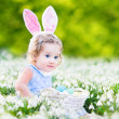 Girl wearing bunny ears playing with Easter eggs — Stock Photo #43249573