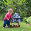 Baby girl playing with a vintage doll stroller — Stock Photo