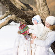 Mother with two children walking in a snowy park — Stock Photo