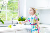 Cute curly toddler girl in a colorful dress washing dishes — Stock Photo