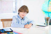 Boy doing his homework at home — Stockfoto