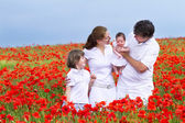 Family with a son and newborn daughter in a red field — Stok fotoğraf