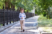 Boy walking on a sunny street — Stock Photo
