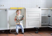 Baby helping to assemble a kitchen in a new home — Stock Photo