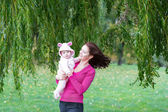 Mother and daughter standing under a colorful willow tree — Stock Photo