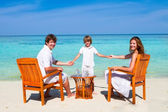 Beautiful family relaxing on a beach — Stockfoto