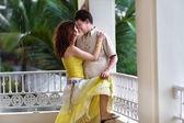 Couple on a balcony in a tropical rain — Stock Photo