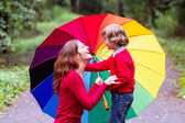 Mother and son under a colorful umbrella — Stock Photo
