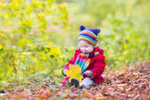 Little baby girl playing with autumn leaves — Stock Photo