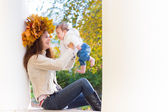 Woman with maple leaves wreath playing with her baby — Stock Photo