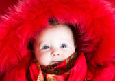 Little baby girl in a red fur jacket — Stock Photo
