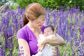 Mother holding baby in a purple flower field — Stock Photo