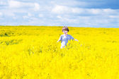 Child running in a field of yellow flowers — Stock Photo