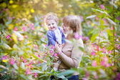 Woman playing with a laughing baby girl in a garden — Stock Photo