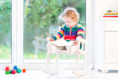 Girl with curly hair wearing a colorful knitted dress reading — Stockfoto