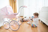 Teenager boy and toddler girl playing together in a white room — Stock Photo
