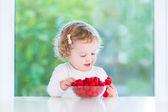 Cute toddler girl eating raspberries — Stock Photo