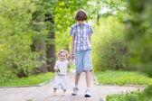 Kluk se svou mladší sestrou v parku — Stock fotografie