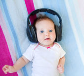 Newborn baby listening to music with huge earphones — 图库照片