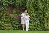 Woman with two kids in formal clothes in the garden — Stock Photo