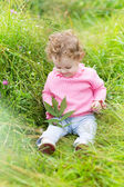 Baby girl playing with a snail — Stock Photo