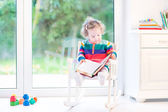 Girl with curly hair wearing a colorful knitted dress reading — Photo