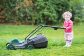 Toddler girl with a lawnmower — 图库照片