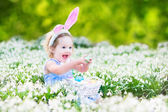 Girl wearing bunny ears playing with Easter eggs — Stock Photo