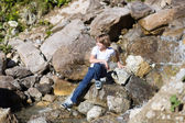 Teenage boy crossing small river — Stock fotografie