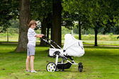 Big brother pushing a stroller — Stock Photo