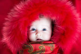 Little baby girl in a red fur jacket — Photo
