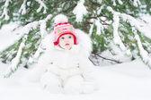 Little baby sitting in fresh snow — Stock Photo
