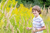 Boy playing in a yellow flower field — Stock Photo