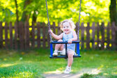 Happy laughing toddler girlenjoying a swing ride — Стоковое фото