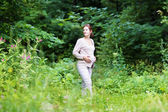 Pregnant woman walking in a park — Stock Photo