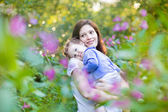 Matka trzyma jej zmęczony córeczkę w parku — Zdjęcie stockowe