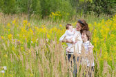 Mother with two kids in a yellow flower field — Stock Photo
