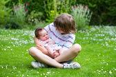 Cute boy holding his newborn sister — Stock Photo