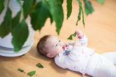 Baby girl lying near a flowerpot — Stock Photo